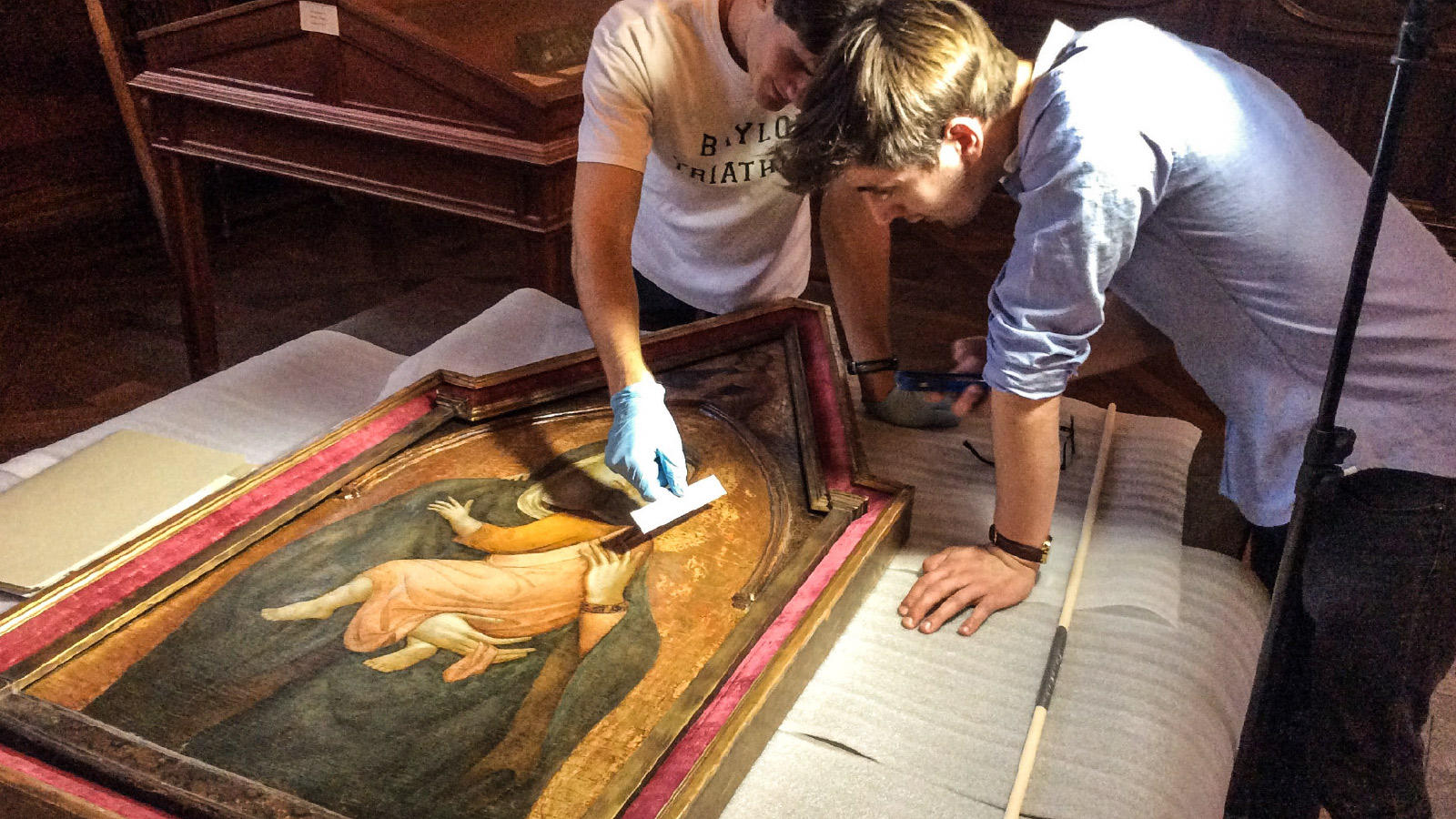 Two University Scholars (Nathan Eberlein, BA '17 and Conner Moncrief, BA '16) in Dr. Hornik's class on Connoisseurship examine a 14th-century Maddona and Child painted by a follower of the Sienese artist Pietro Lorenzetti in the Armstrong Browning Library Collection. The Connoisseurship class was held in the Armstrong Browning Library in from of the 15 original works of art from 1330-1750. The Maddona and Child here is removed from the wall to investigate not only the condition of the work (i.e. insect presence, paint deterioratoin) but also to measure the punch marks in the Virgin's gold-leaf halo. The punch marks, are in effect, a type of signature for a particular painting workshop during this period and assist in formulating accurate attribution.