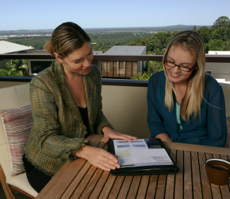 photo of a businesswoman showing a woman a tablet computer