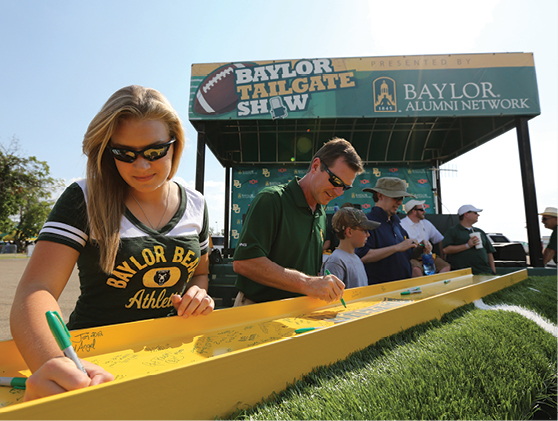 Students sign an I-beam for McLane Stadium's build