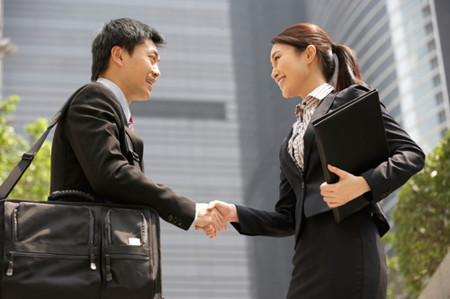 Stock photo of a businessman and businesswoman shaking hands