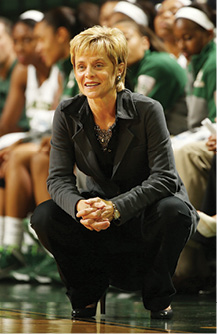 Photo of Coach Kim Mulkey in her signature crouch position on the sideline of a game