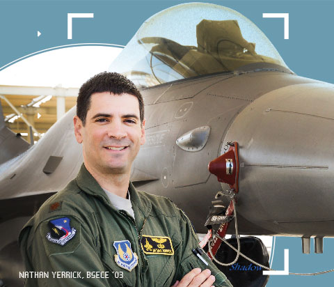 Major Nathan Yerrick poses with arms crossed in a flight suit, backed by a fighter jet