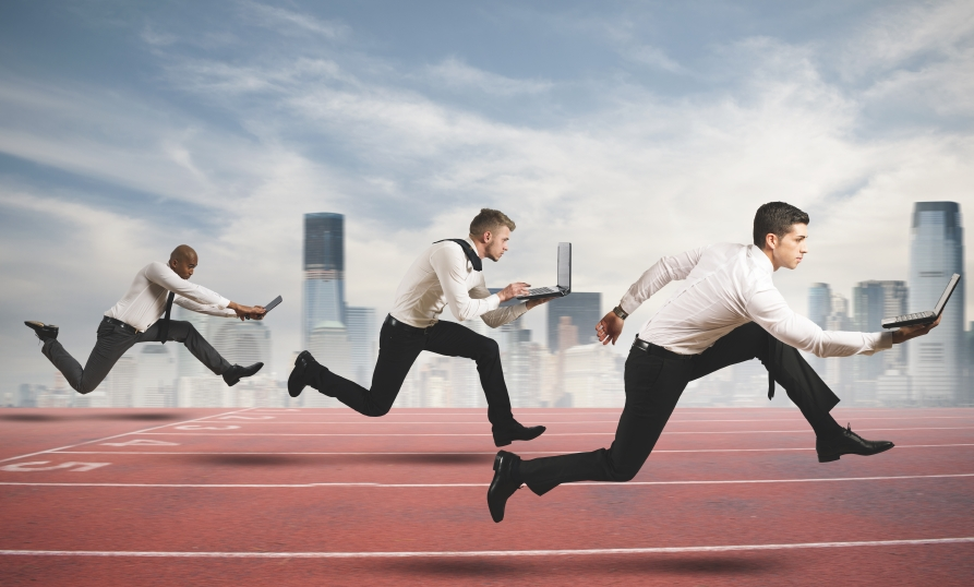 stock photo representation of businessmen carrying open laptops in a sprint race