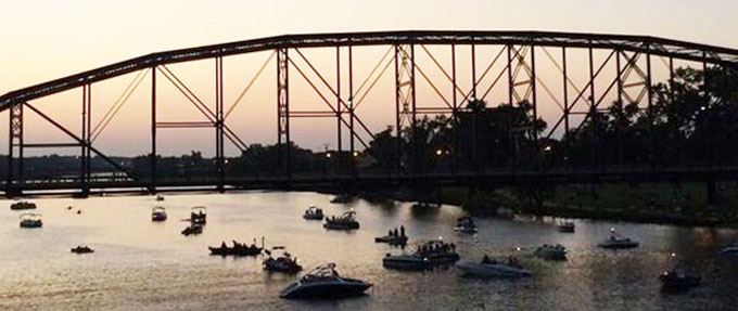 Image of boats on the Brazos river at sunset