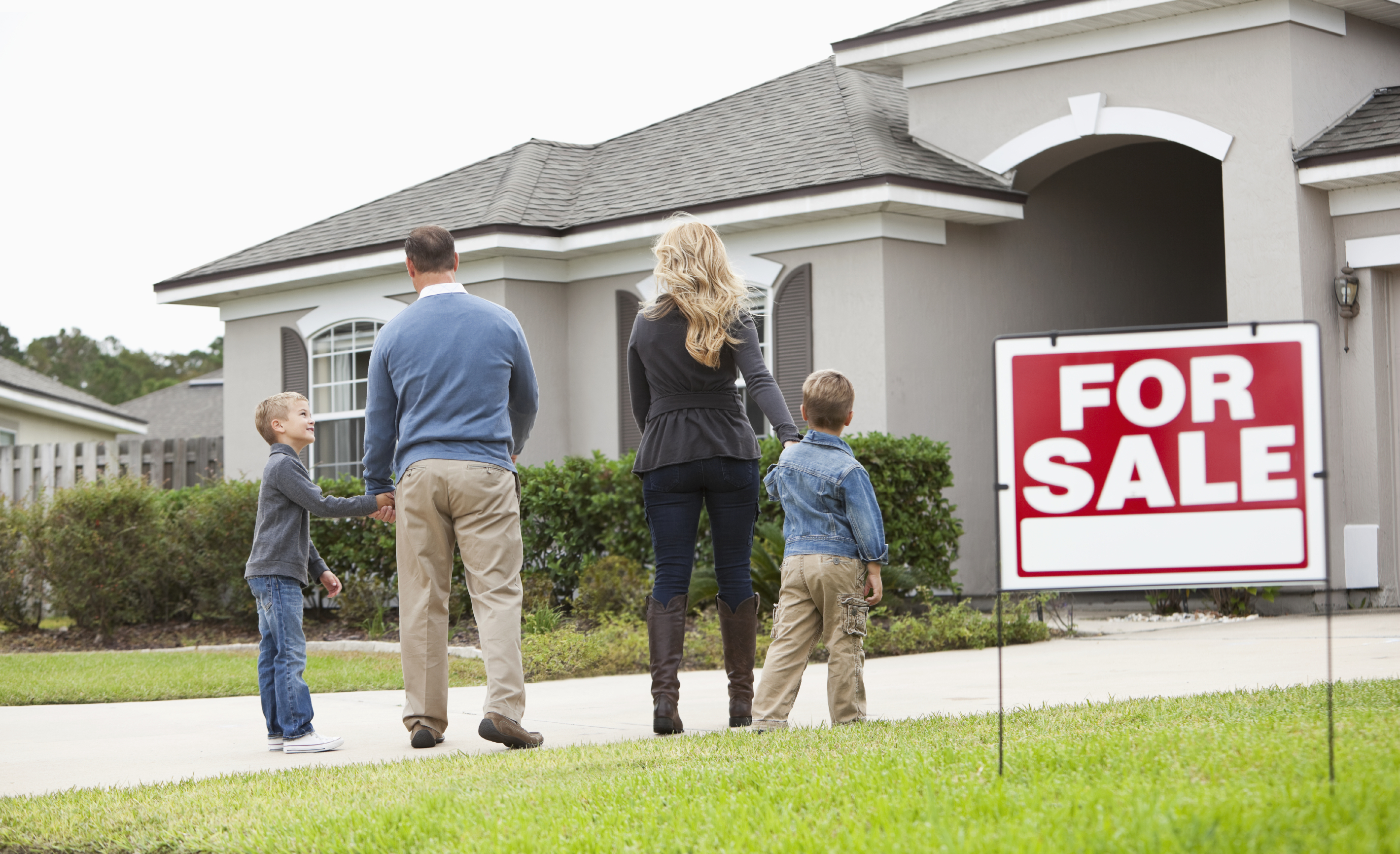 Stock photo of family in front of a home for sale