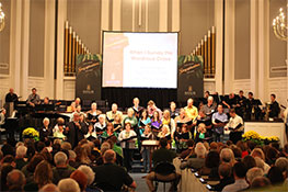 A choir gathers in a performance hall, filled with audience members
