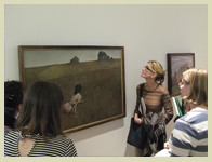 Students study a painting in a gallery
