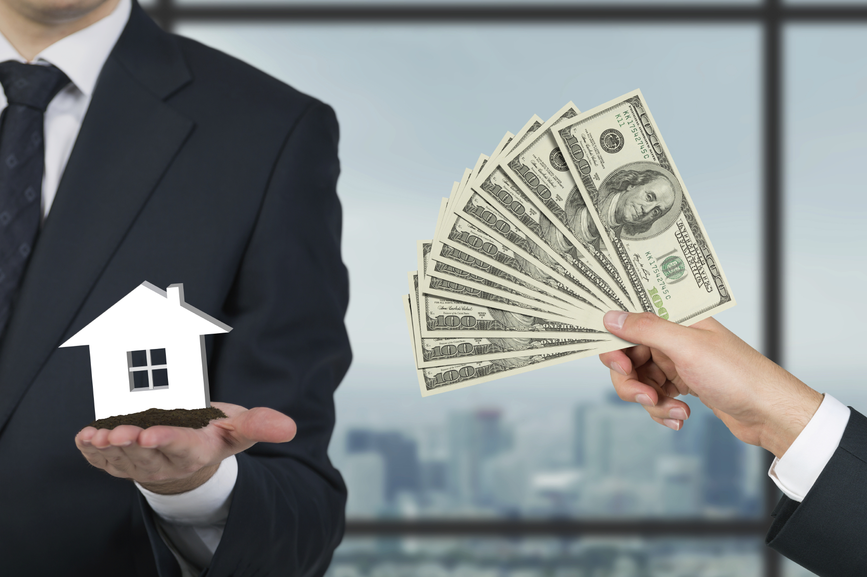 Stock photo of money exchanged for a house