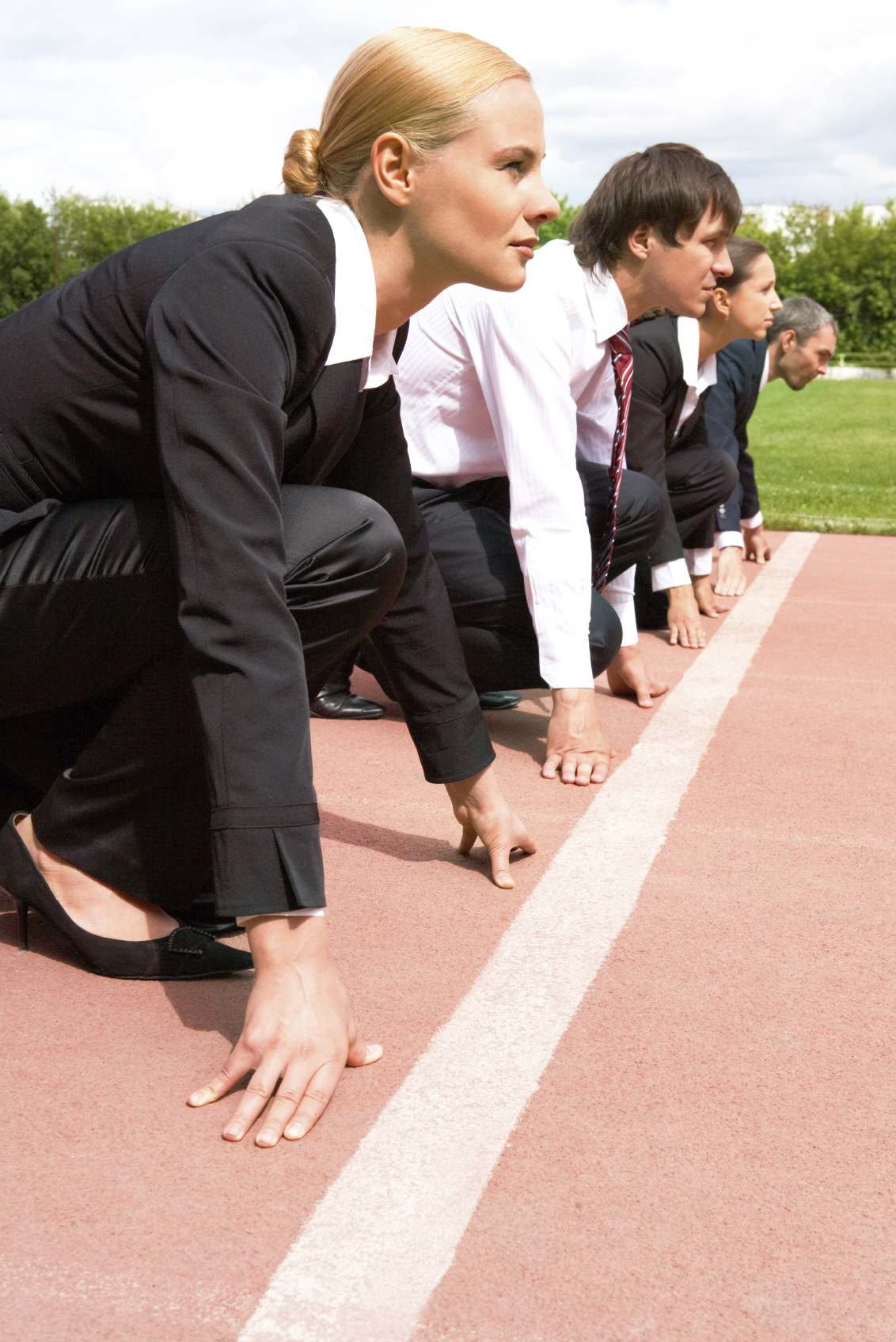Stock photo of business men and women in business attire at the starting line of a track