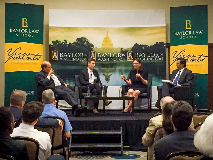Four panelists sit on stage, discussing Encryption and National Security