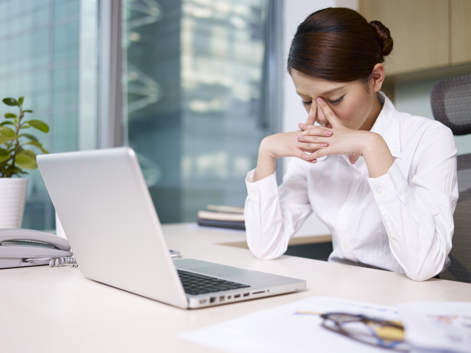 Stock photo of a businesswoman thinking at her desk, disappointedly