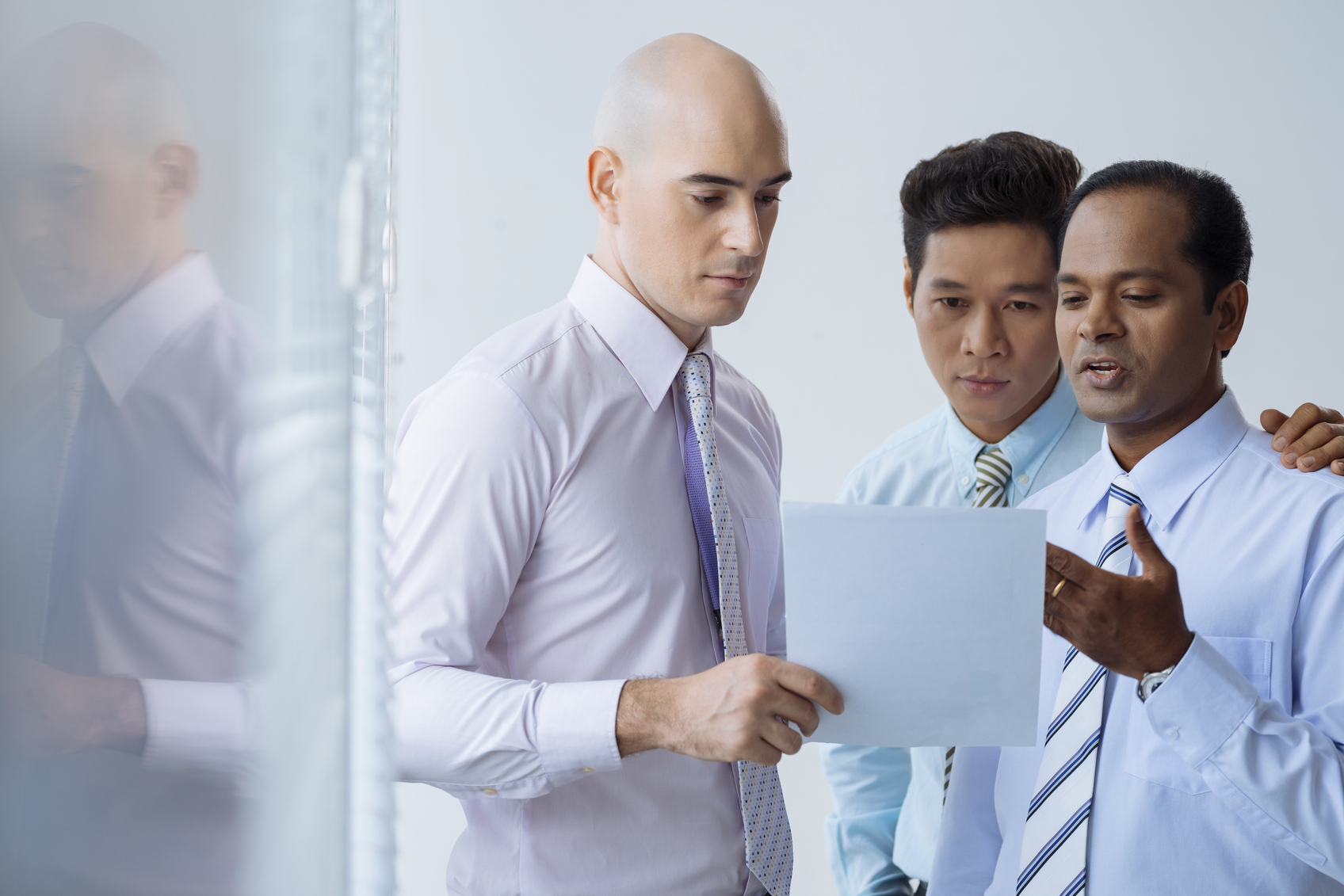 stock photo of three businessmen looking at a piece of paper