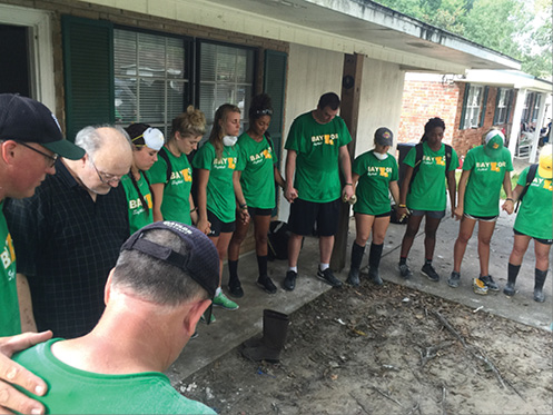 A group of volunteers from Baylor bow their heads in prayer