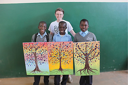 Photo of a student on a mission trip showing off artwork of orphan students in Zambia