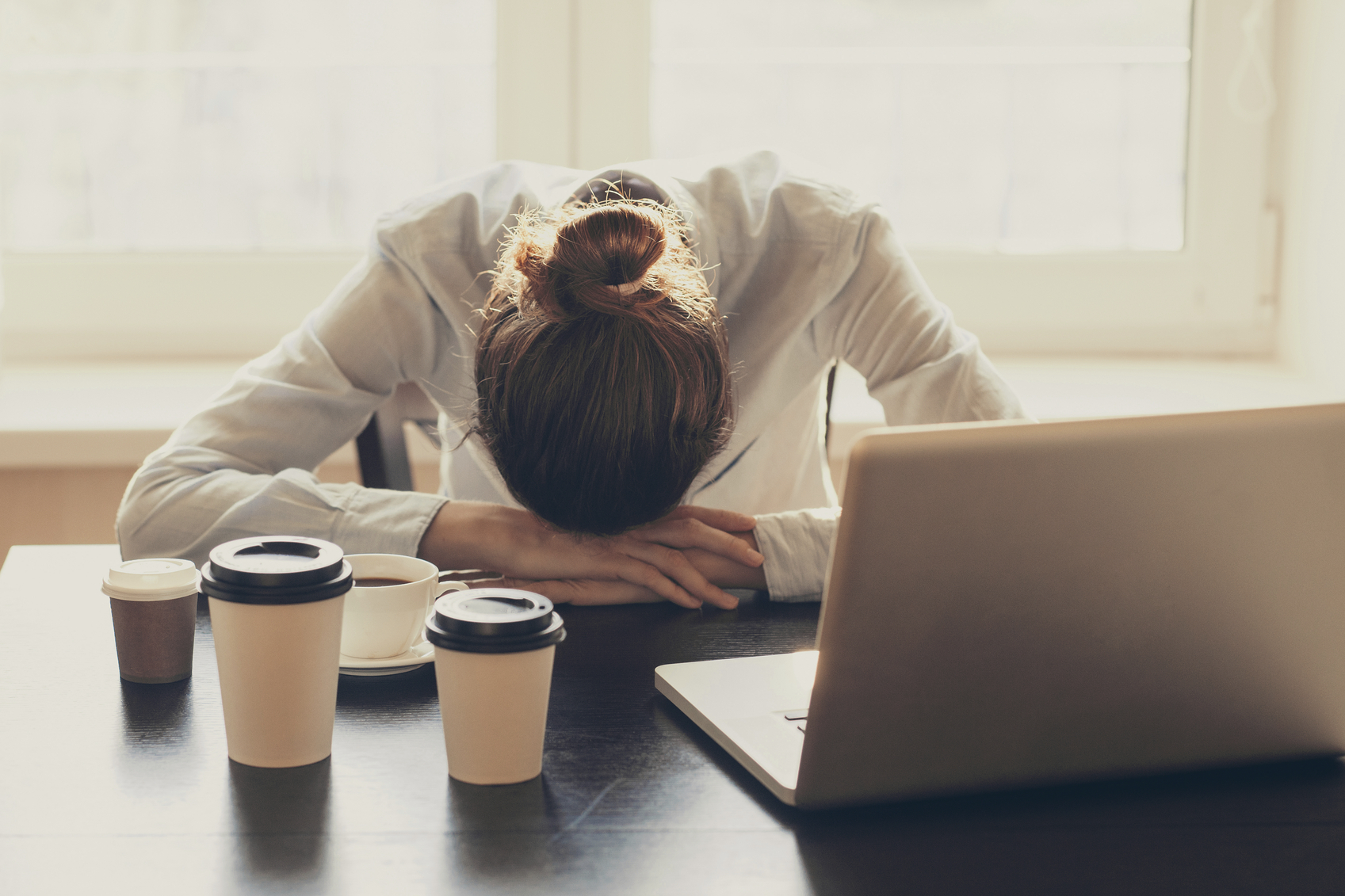 Stock photo of a business woman with her head on the desk