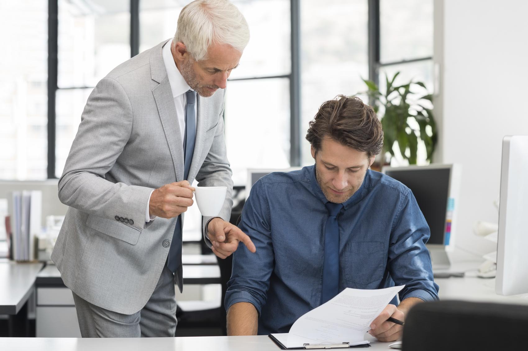 Stock photo of an elder businessman guiding a younger businessman