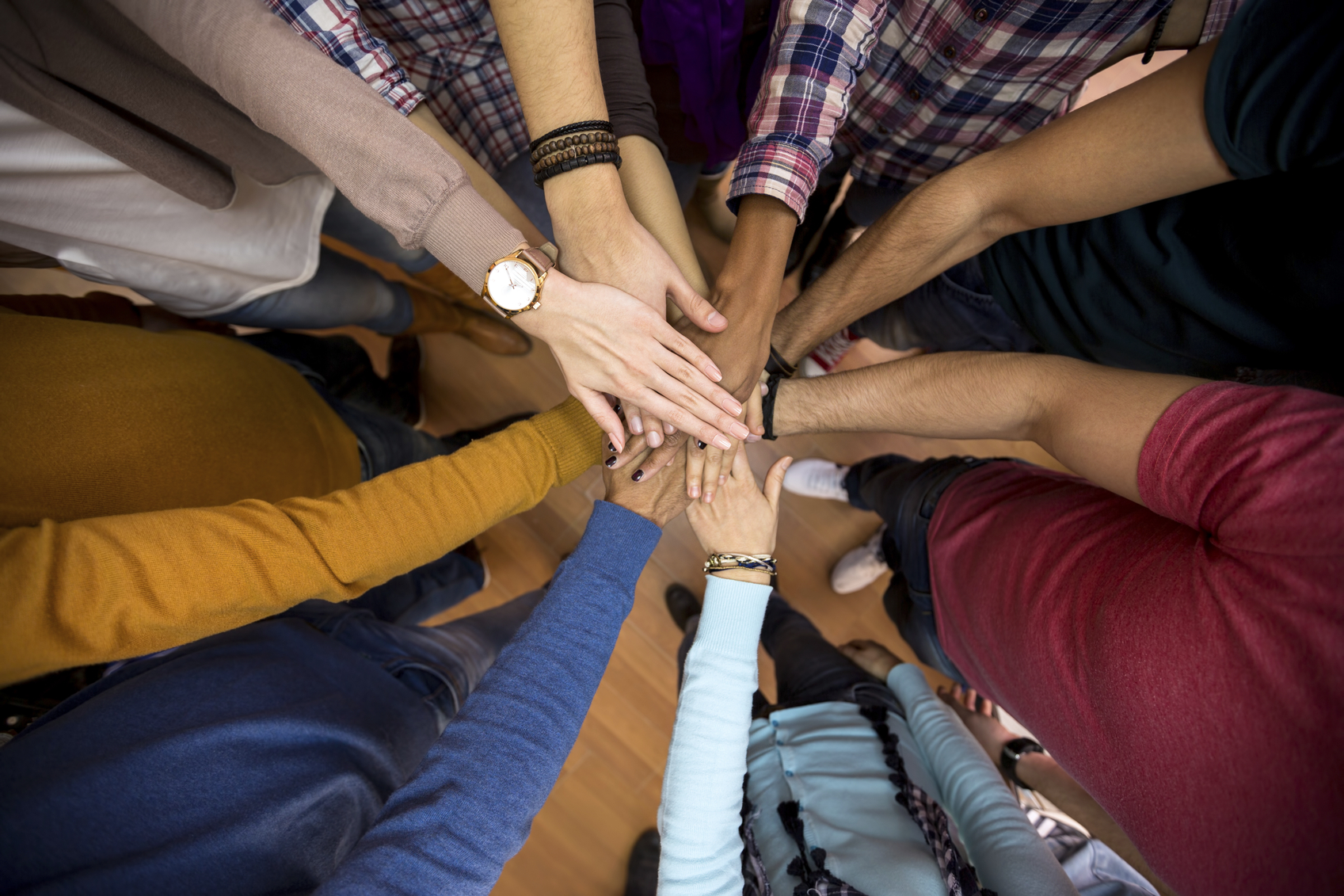 Stock photo of a group who all has one hand extended to meet