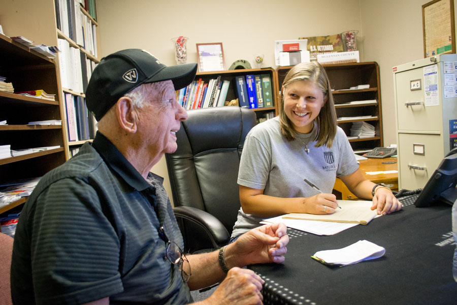 A female Baylor Law student guides a veteran through some difficult paperwork