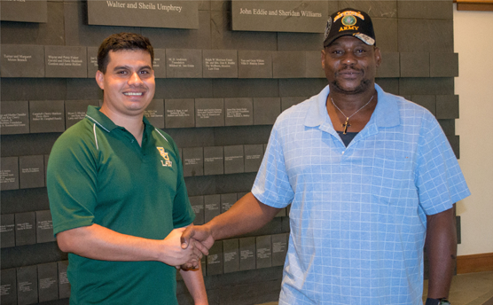 A veteran shakes the hand of the Law Student who helped him
