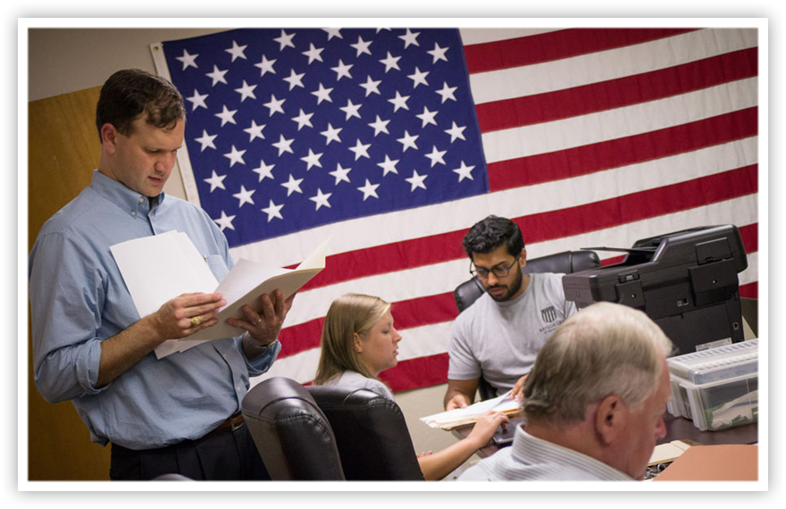 A veterans law clinic takes place in a classroom decorated by an American flag