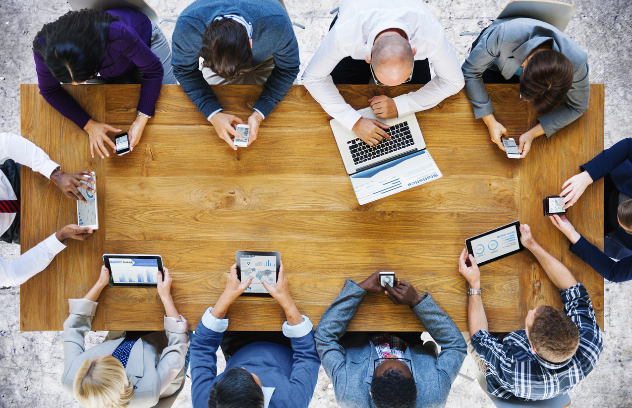 Stock photo of a business meeting with everyone on an electronic device