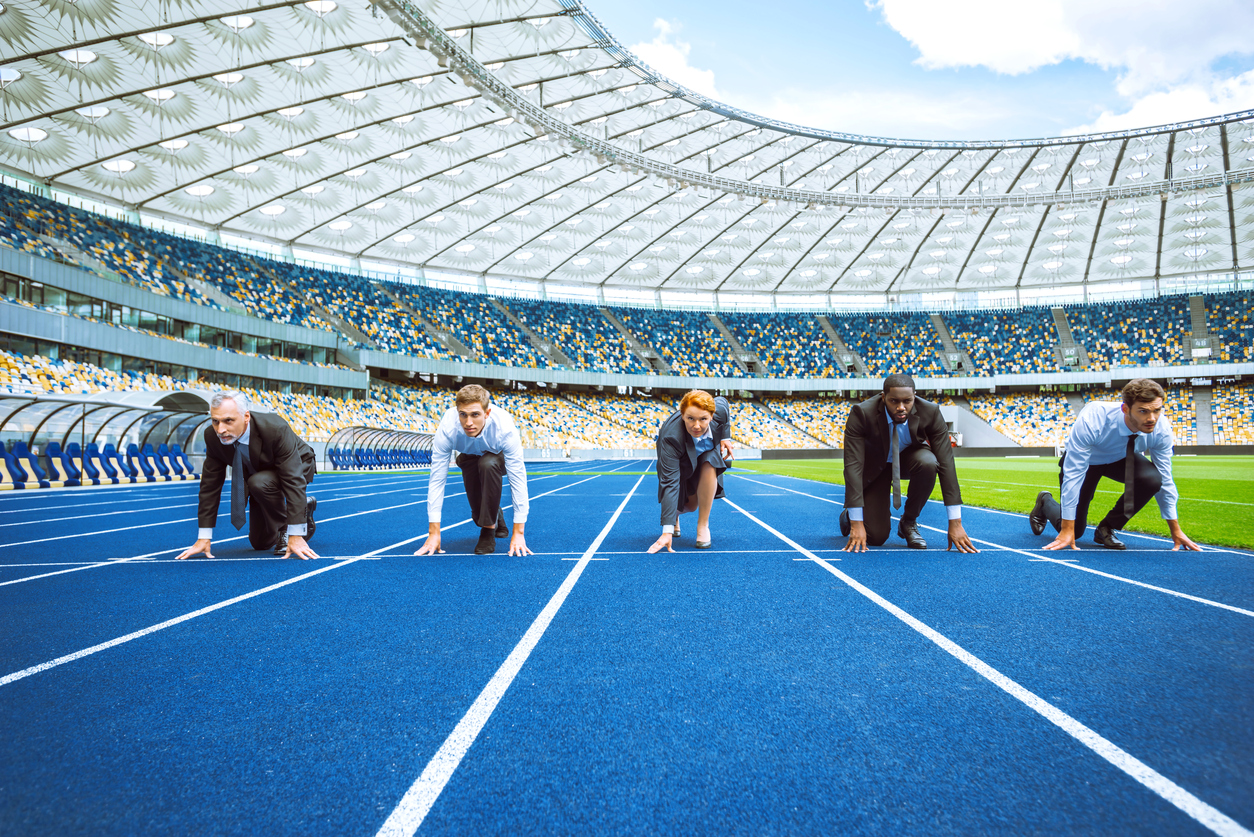 Stock photo of men and women in office attire at the starting line of a track