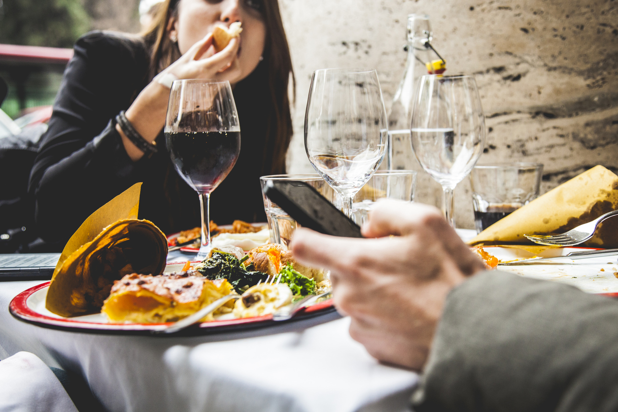 Stock photo of man and woman at dinner, with phone in man's hand