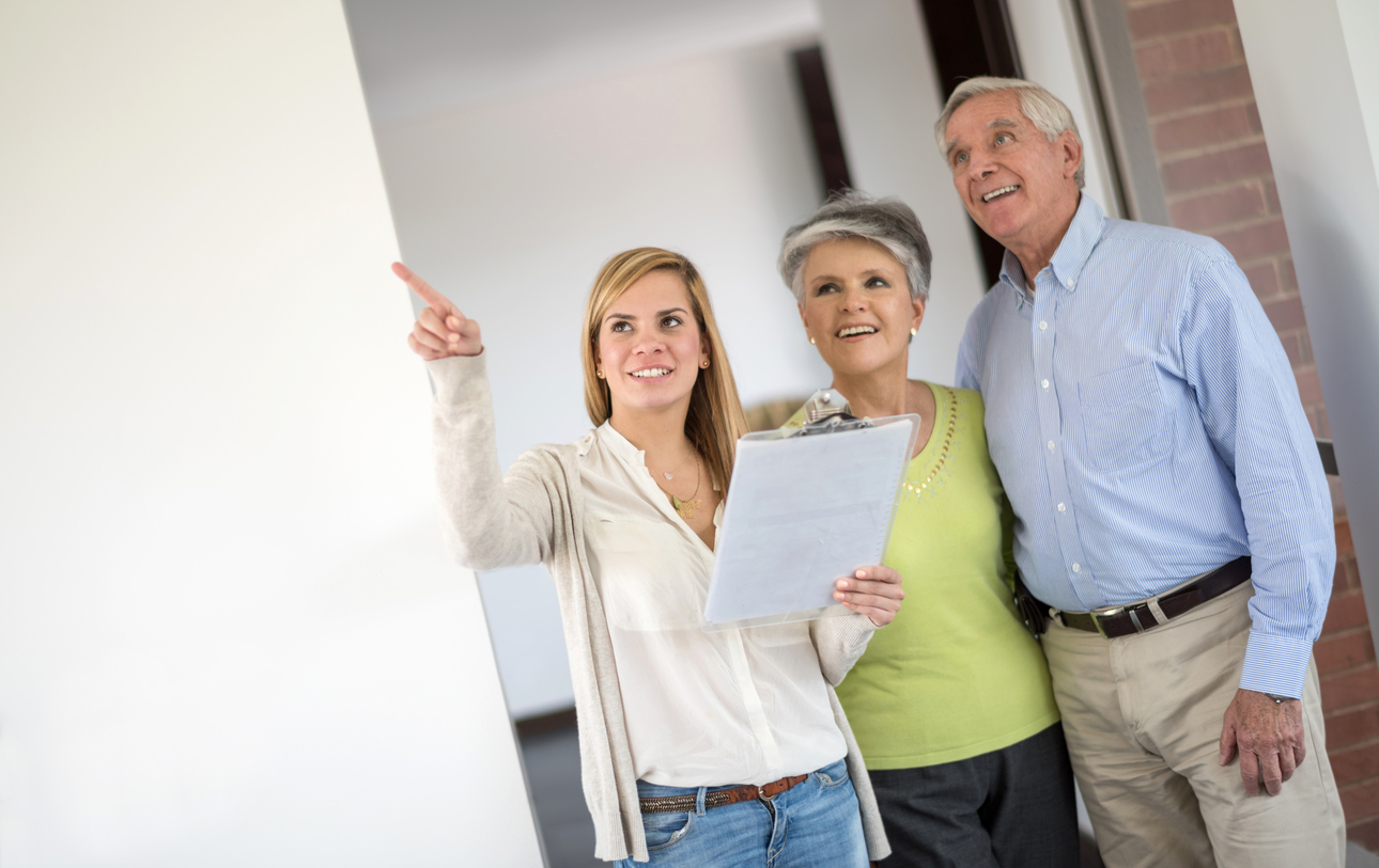 Stock photo of a businesswoman showing a couple a home