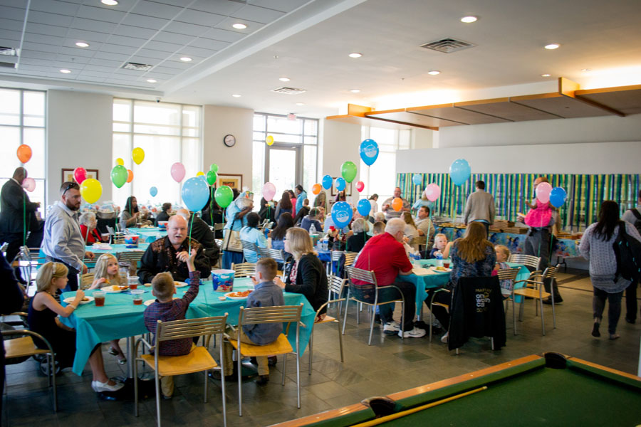 A room is full of merriment, with children and balloons aplenty