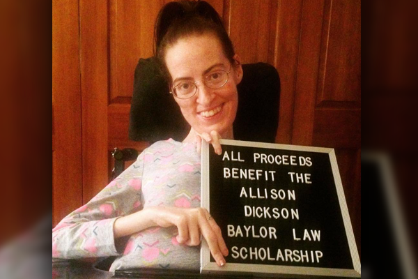 Photo of Allison holding up a sign to promote the scholarship and generate funds