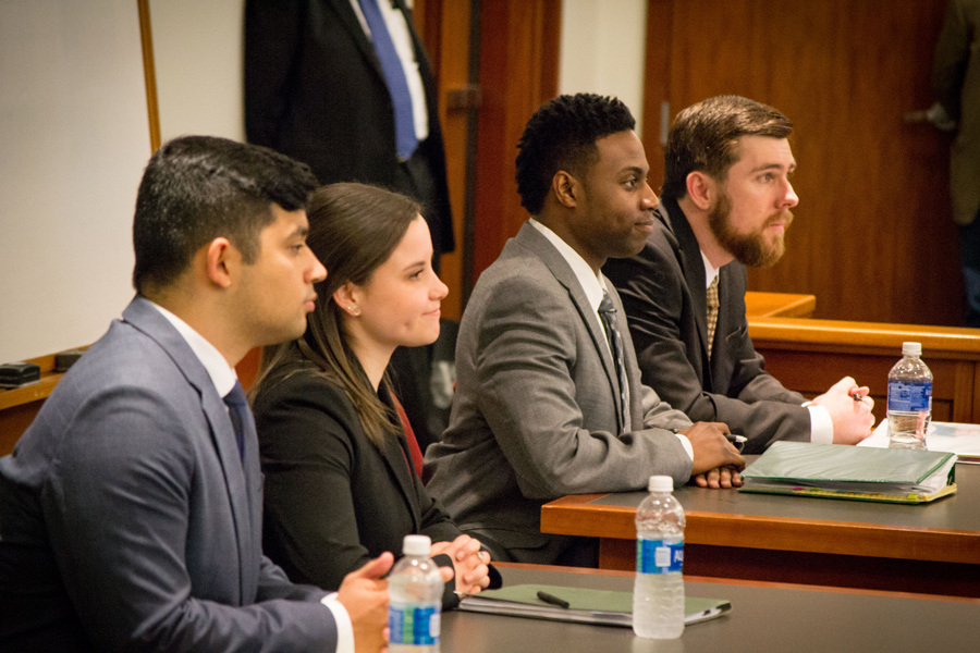 Trial Advocates in training pay rapt attention to a teacher in a courtroom