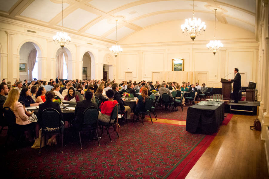 A hall full of attentive attendees gathers in a lecture hall
