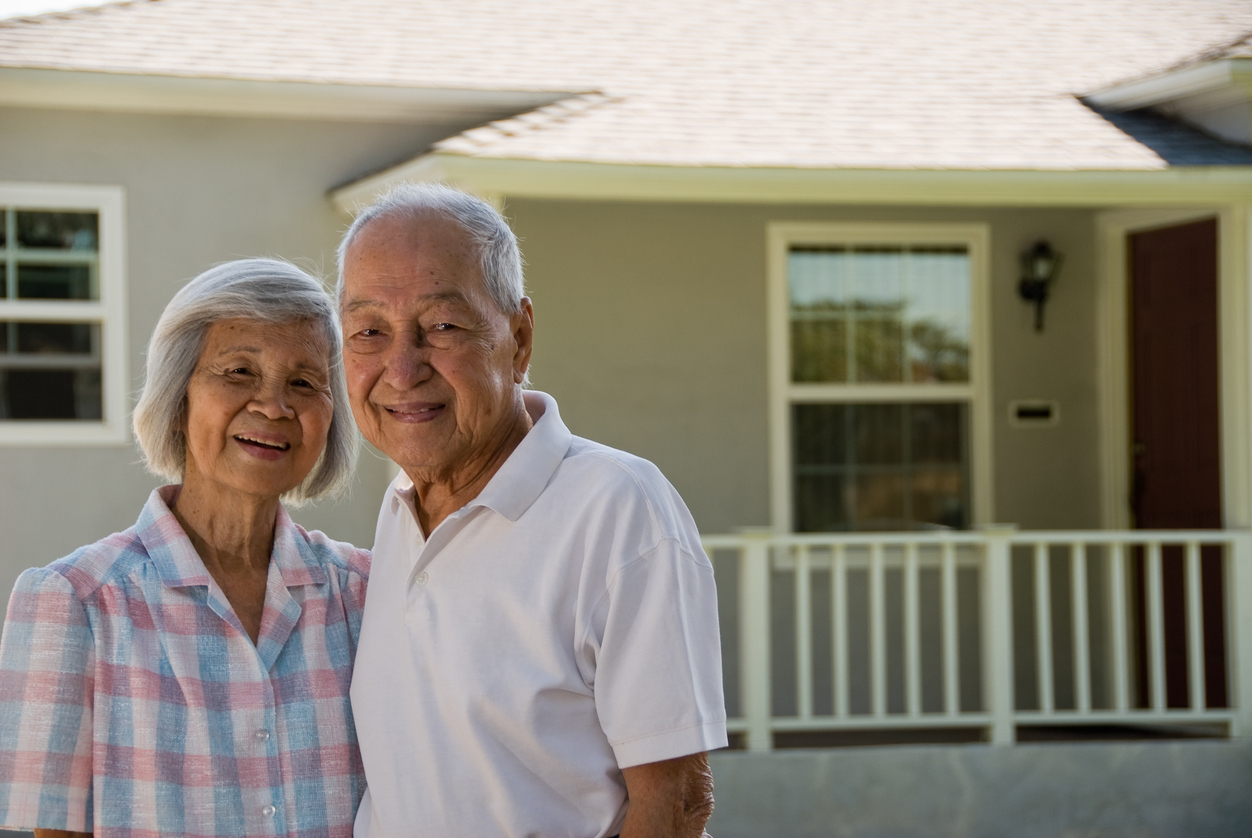 Stock photo of elderly couple in front of a home