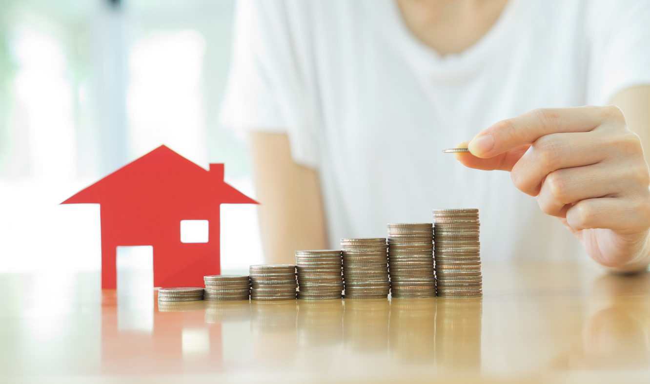Stock photo of coins stacked like a bar chart, next to a miniature house