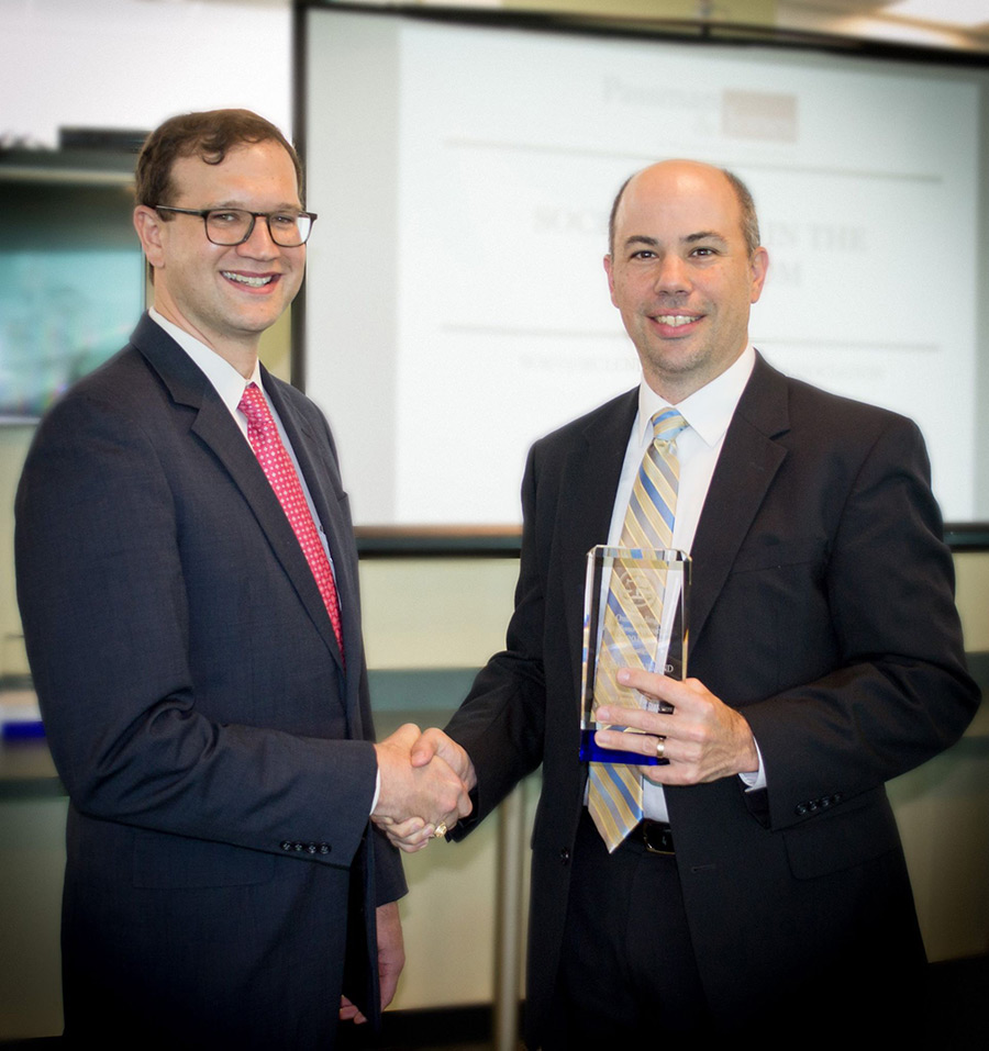 Josh Borderud presents Michael Bourland with an award for advocacy
