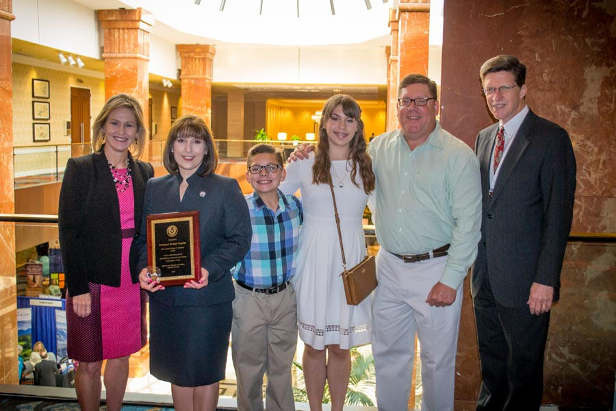 Professor Fuselier is surrounded by family and Dean Toben as she holds the award