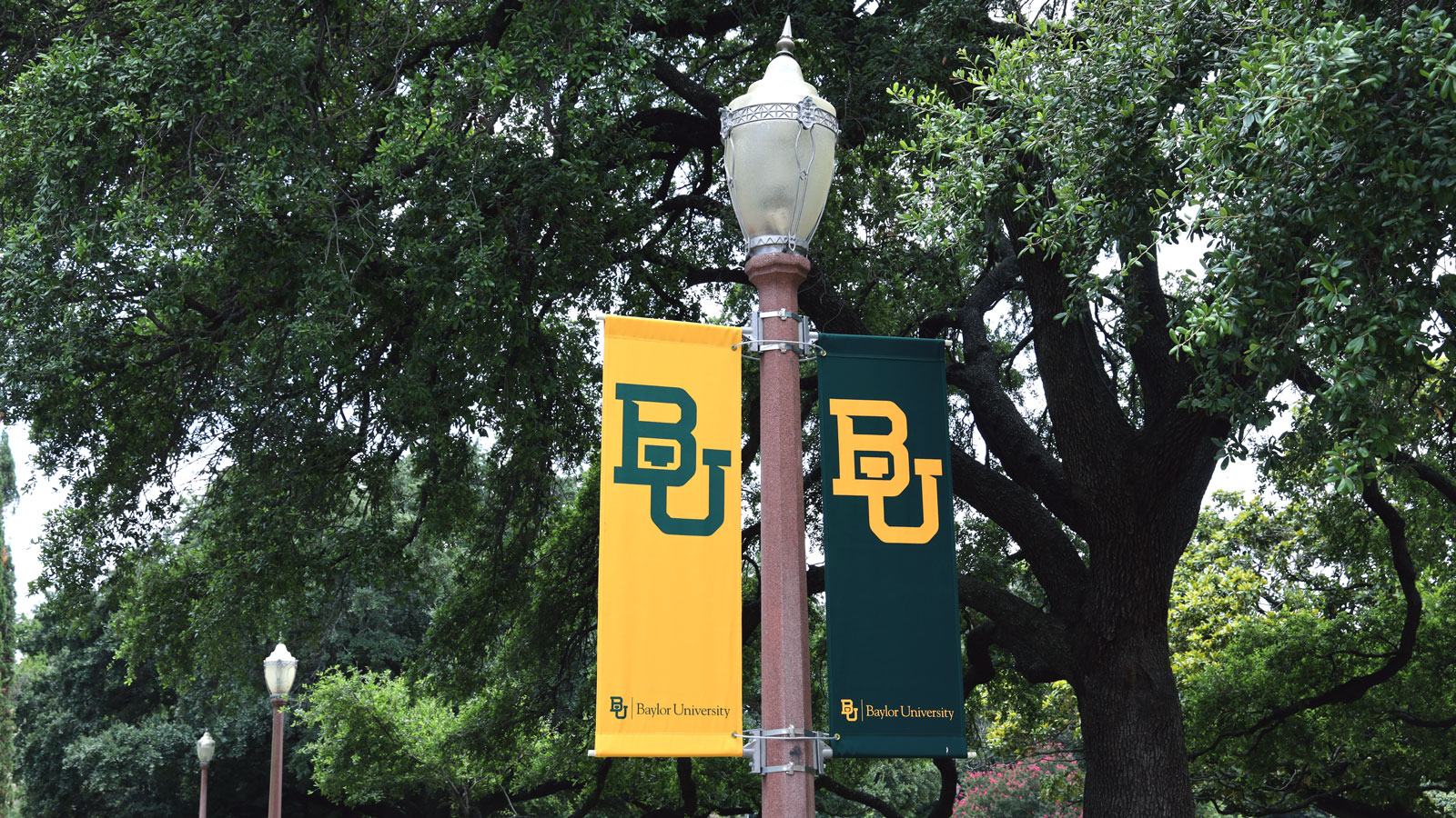 As the sun sets on Baylor's campus, memorial lampposts adorned with Baylor banners light the ways of time.