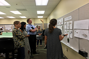 Students study a wall display of various design presentations