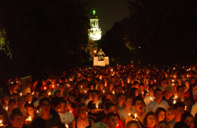 Candles light the faces of freshmen at the Mass Meeting