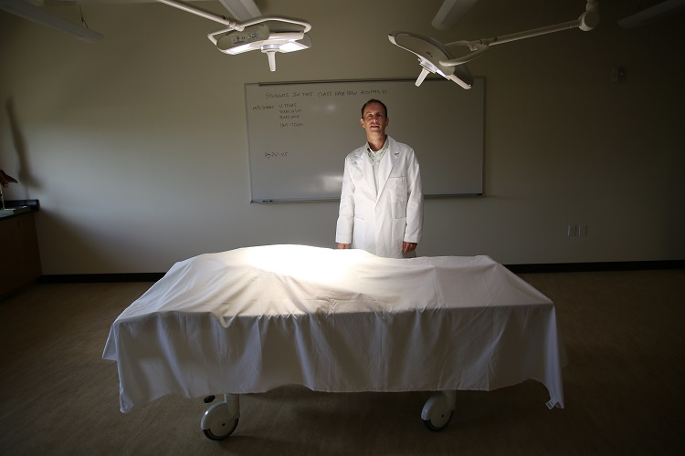 Photo of a doctor behind a covered body on a gurney
