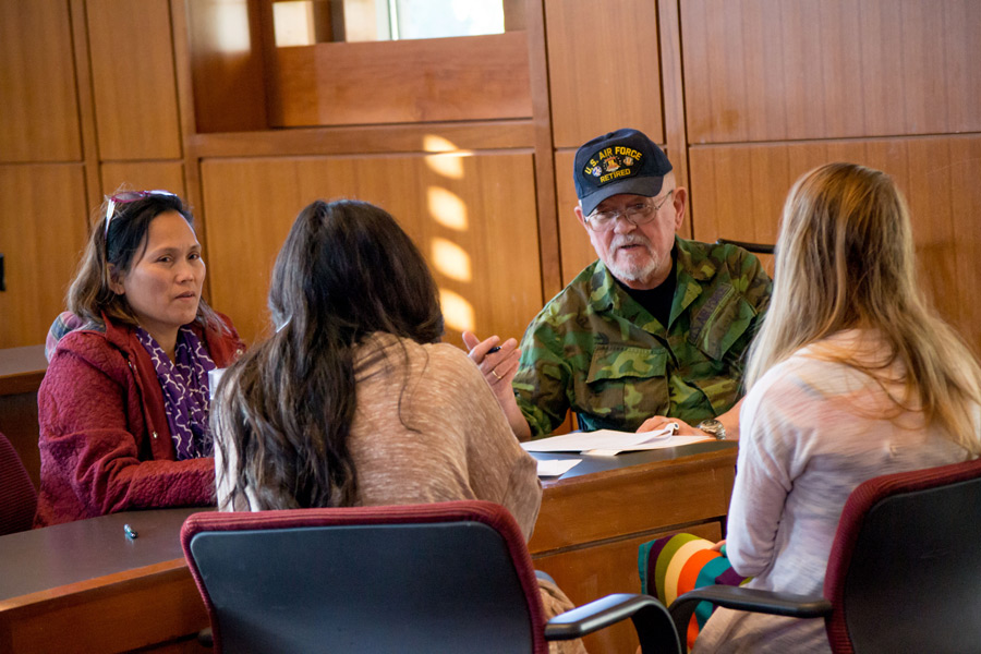 A group of Baylor Law students sits in a court classroom with a veteran