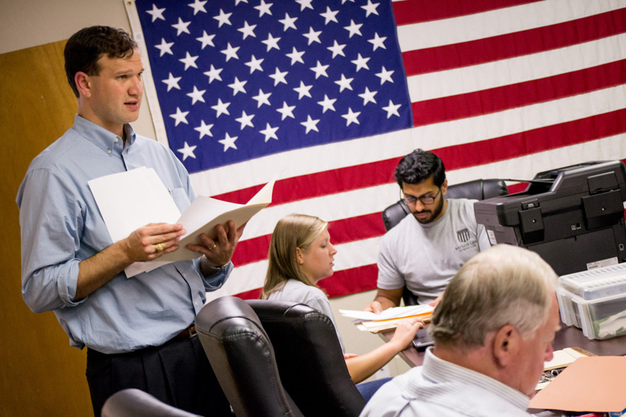 Josh Borderud stands with papers in hand and an American Flag backdrop