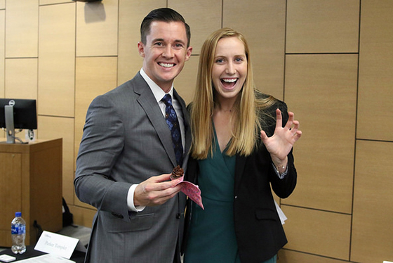 A male and female student pose for the camera in business attire, giving a Sic 'Em to the camera