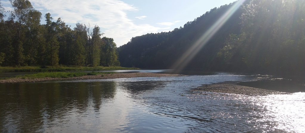 A serene picture of a river, lit by sunbeams