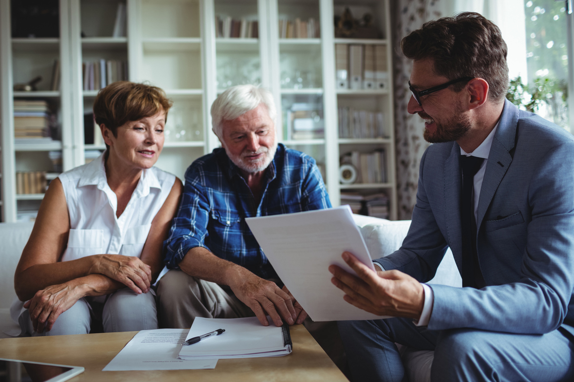 Stock photo of a smartly dressed businessman explaining things to an elderly couple