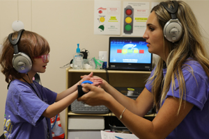 Both wearing headphones, a medical professional and a child patient do listening exercises