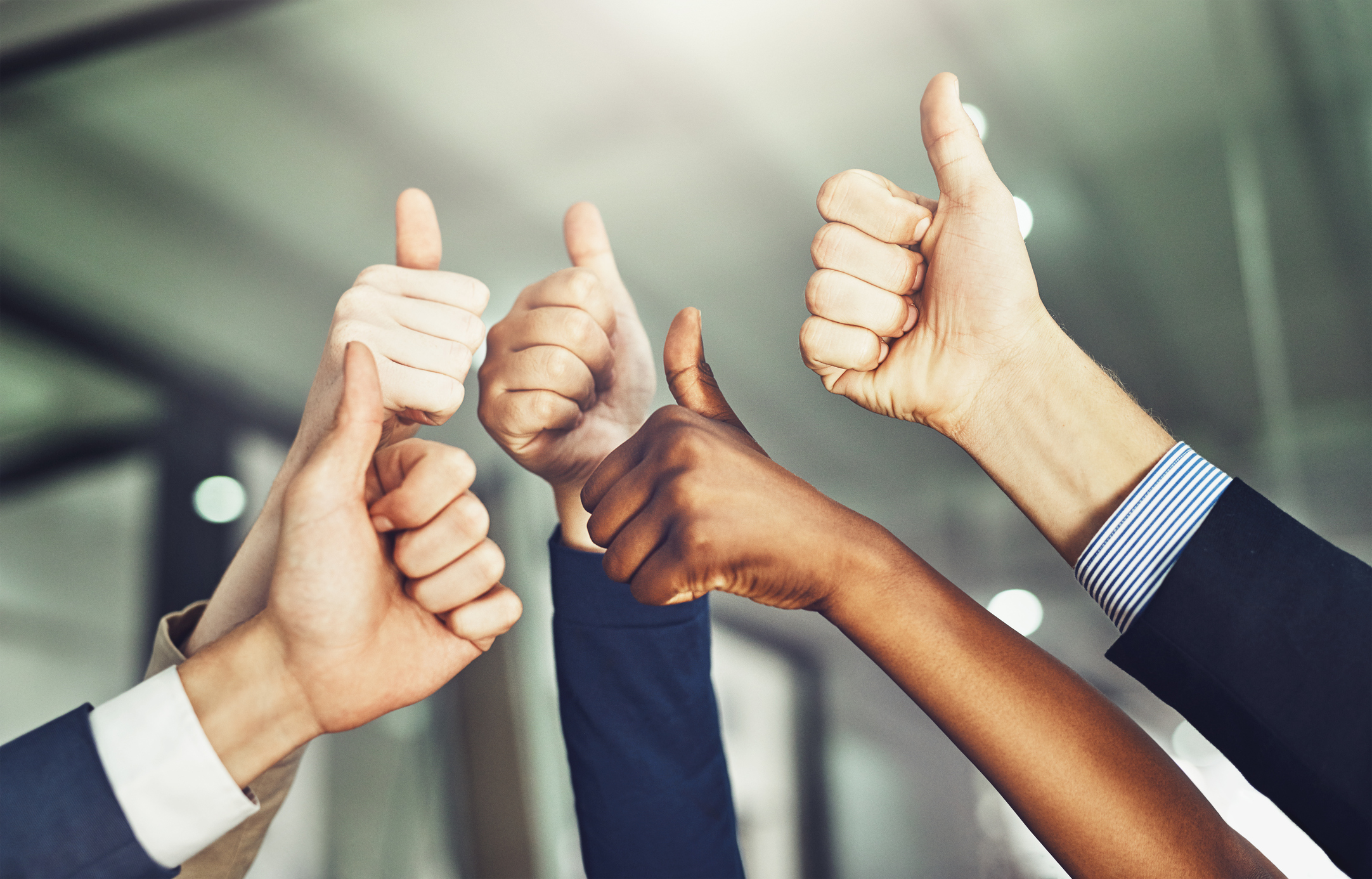 Stock photo of group holding thumbs in the air