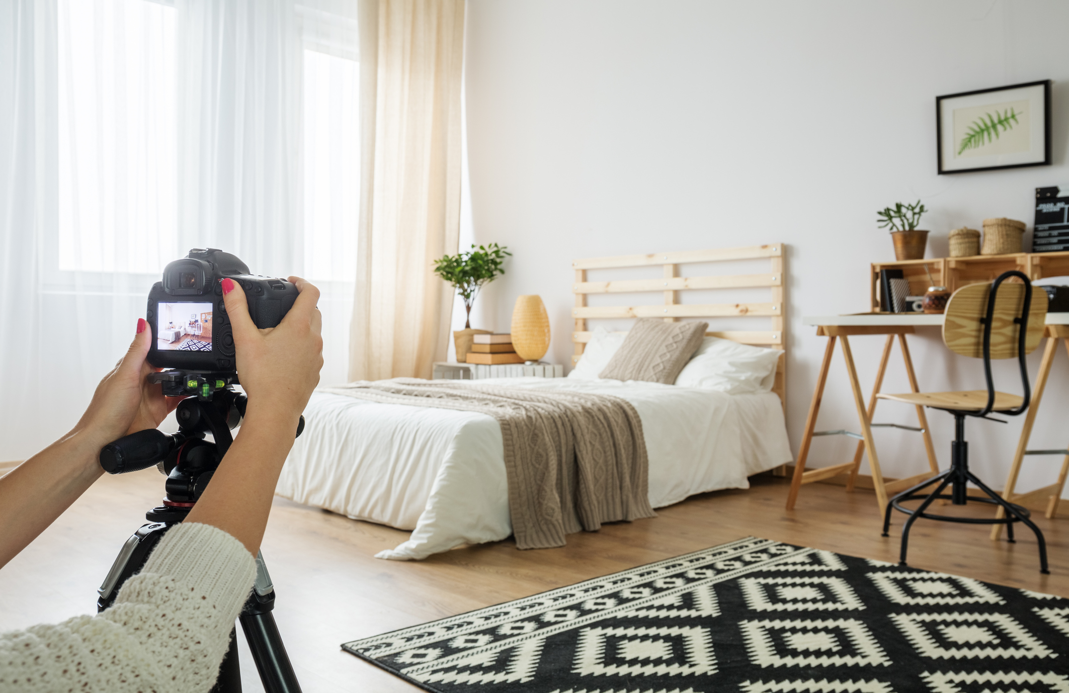 Stock photo of a photographer taking photos of a bedroom