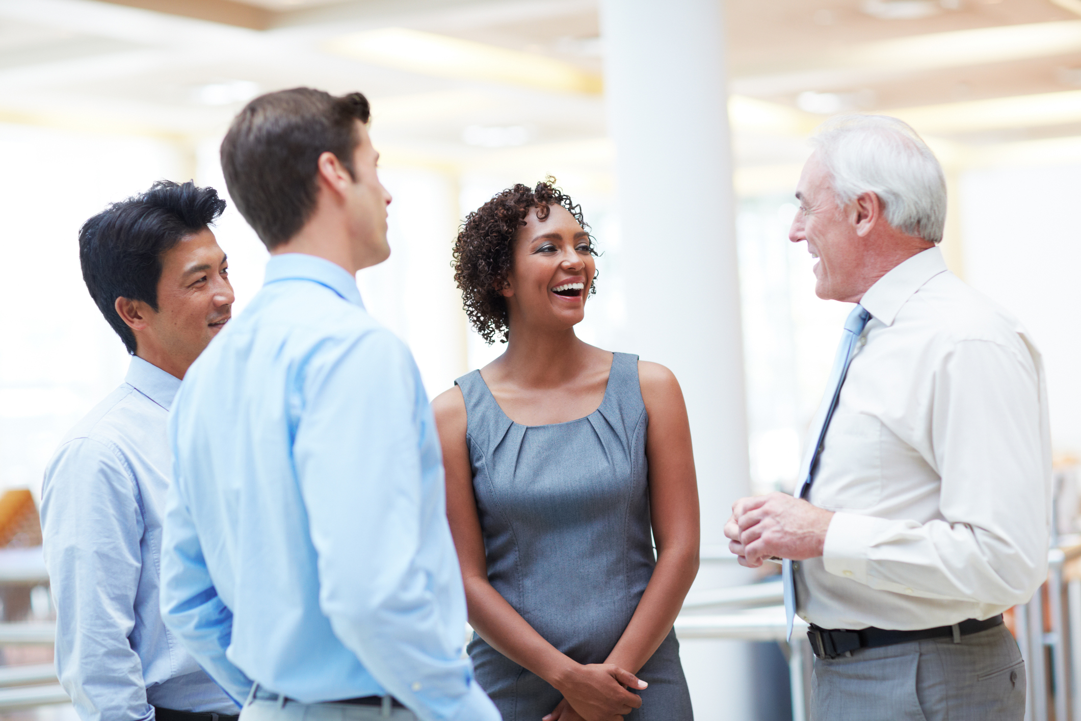 Stock Photo of businessmen and women meeting and laughing