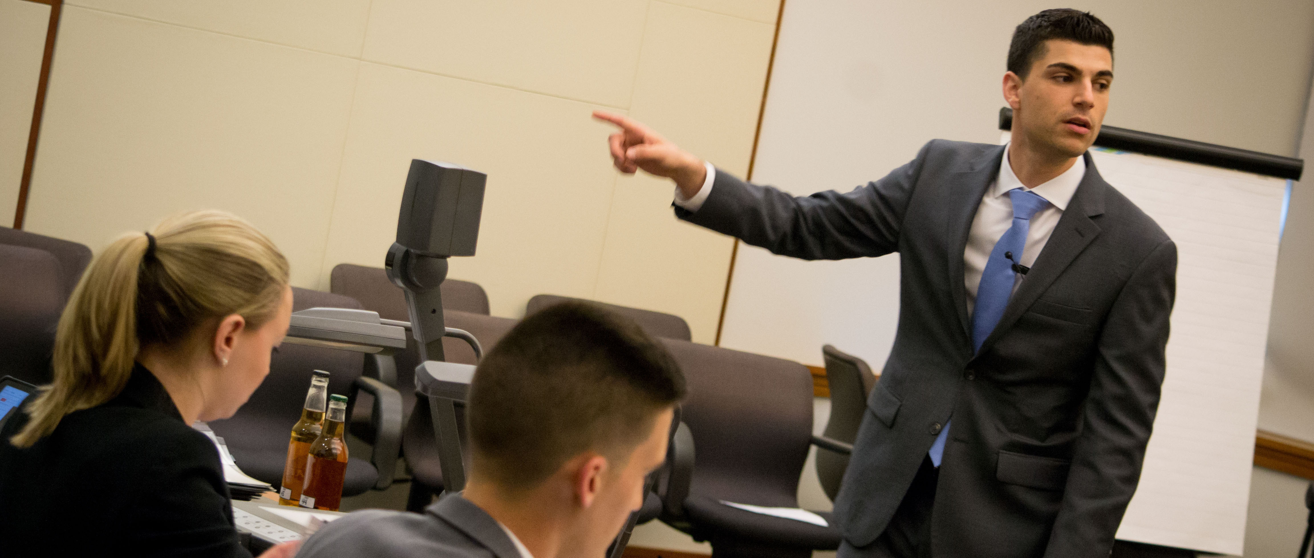 Phillip Pasquarello emphatically makes a point in a business suit, pointing toward the evidence